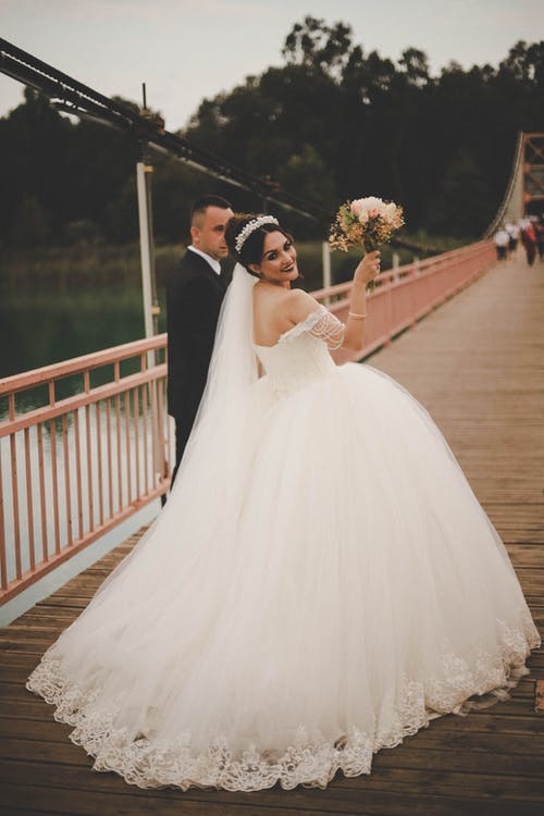 Couple walking on footbridge during wedding day