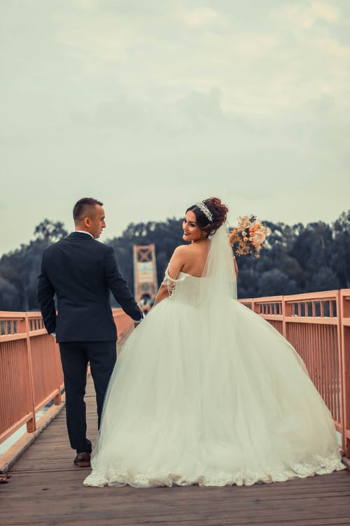 Cheerful couple in wedding outfits enjoying romantic walk