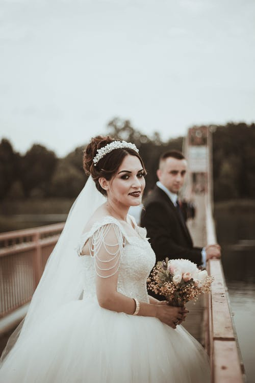 Married couple standing on bridge during romantic wedding day