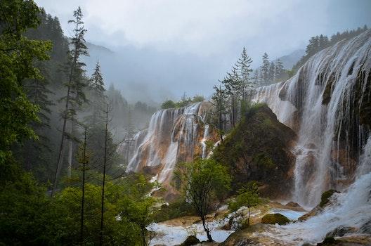 Waterfalls in Yellow Rocks Under White Foggy Sky