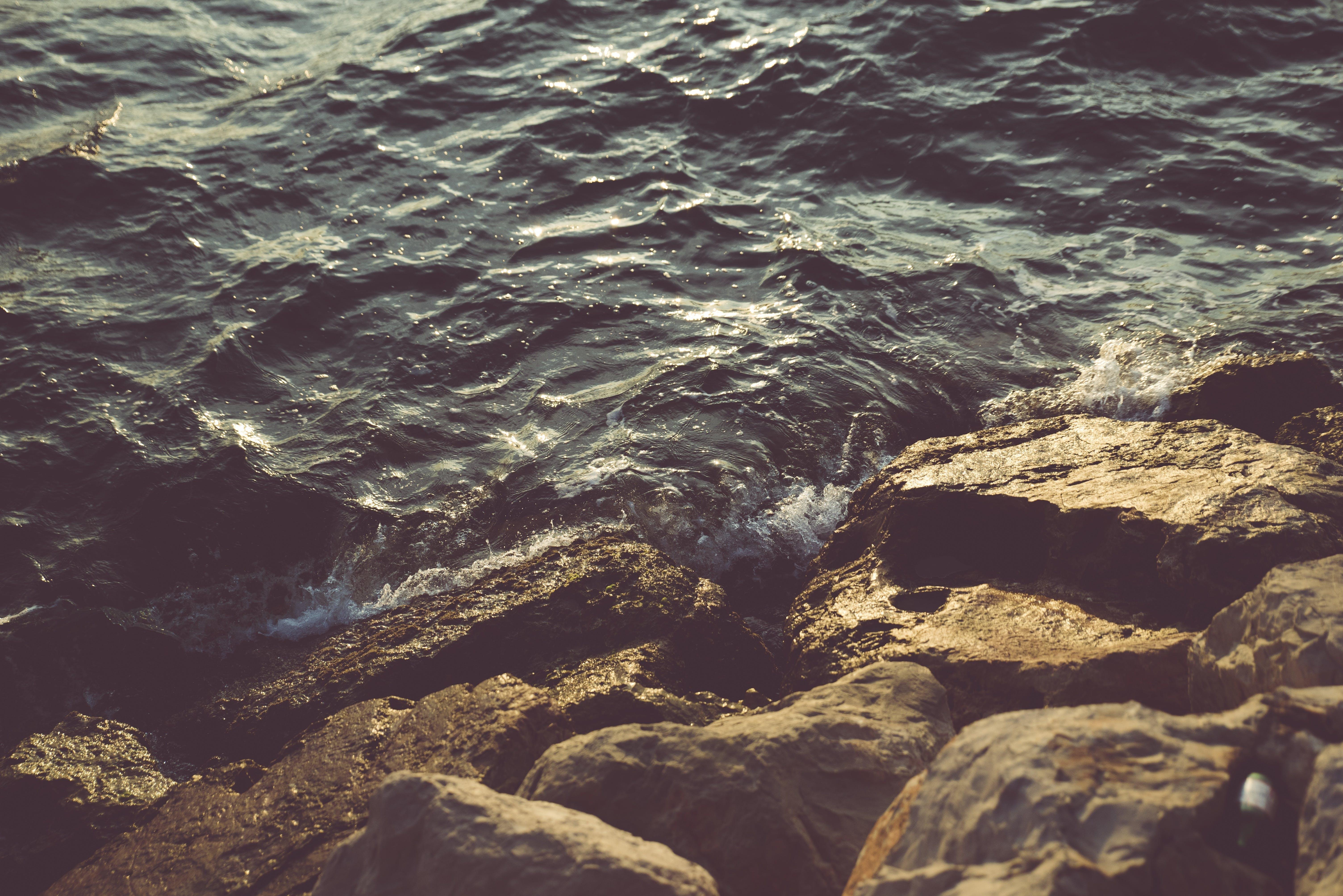 Ocean Wave Toward Brown Rocks during Daytime