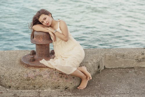 From above full body of barefoot resting on waterfront while leaning on bollard and looking at camera