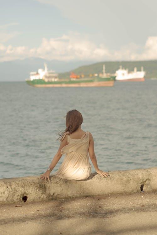 Woman sitting on embankment near rippling sea