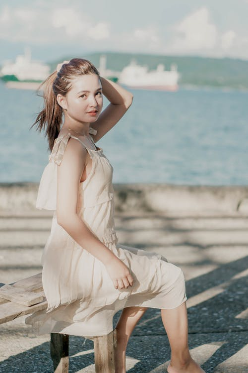 Positive woman in summer dress resting on waterfront