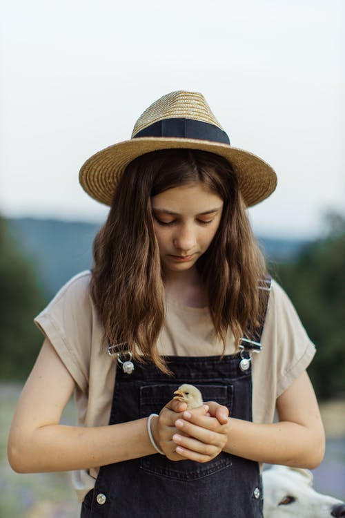 Close-Up Shot of a Girl with Sun Hat Holding a Chick