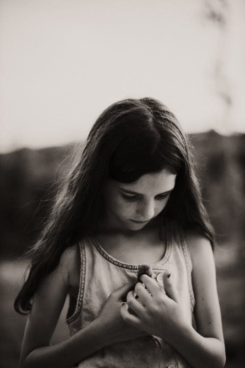 Grayscale Photo of a Girl Holding a Chick