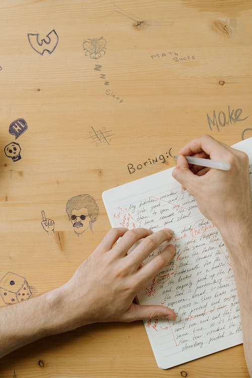Person Writing on Wooden Surface