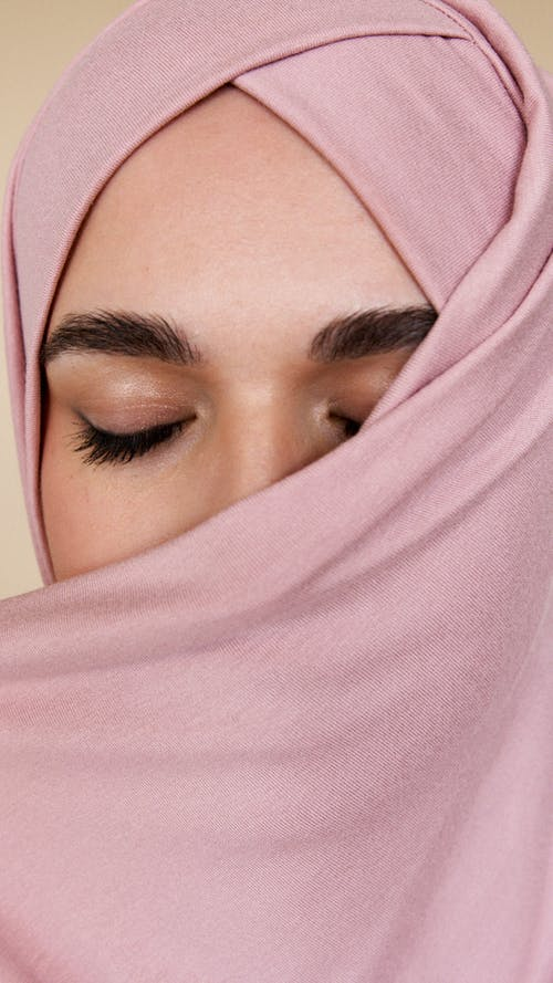 Woman in Pink Hijab Covering Her Face With Pink Textile