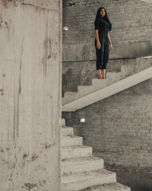 Man in Black Shirt and Orange Pants Walking on Gray Concrete Staircase