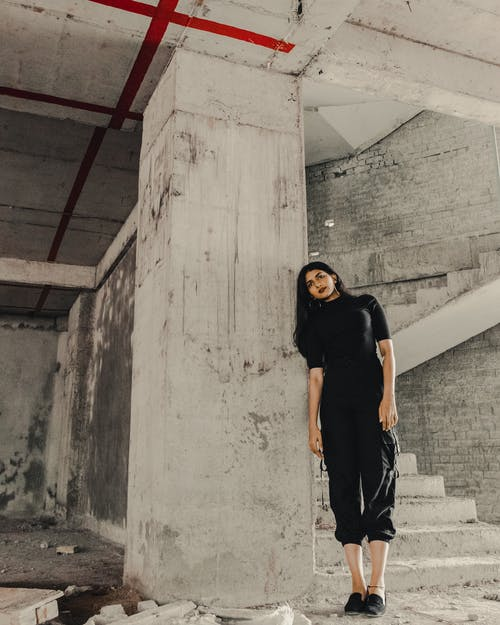 Woman in Black Crew Neck T-shirt and Blue Denim Jeans Standing on Gray Concrete Stairs