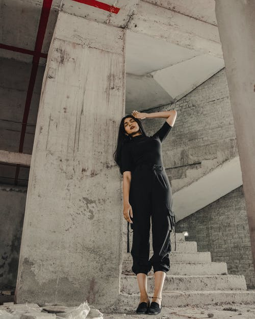 Woman in Black Long Sleeve Shirt and Black Pants Standing on Gray Concrete Stairs