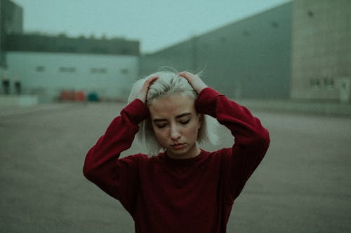 Girl in Red Sweater Standing on Gray Concrete Floor