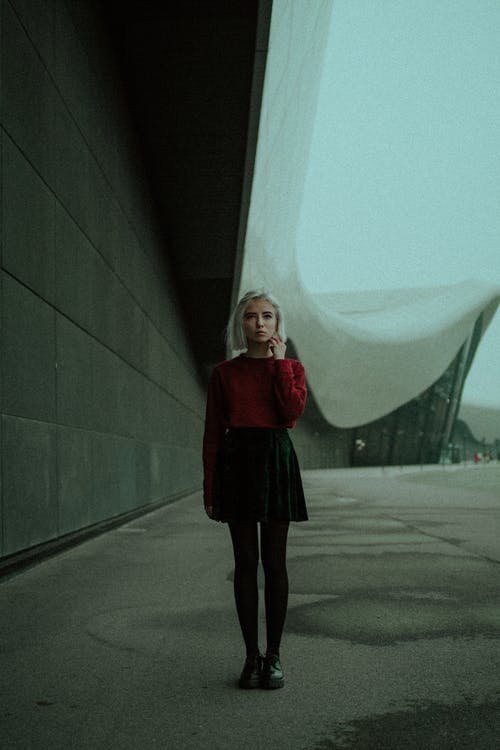 Contemplative woman standing near modern building in haze