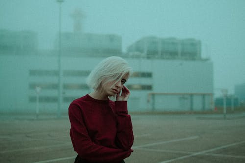 Frustrated woman standing in foggy desolated area