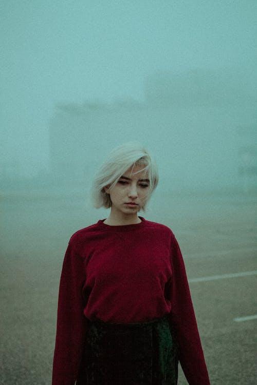 Preoccupied sad woman standing in dense fog