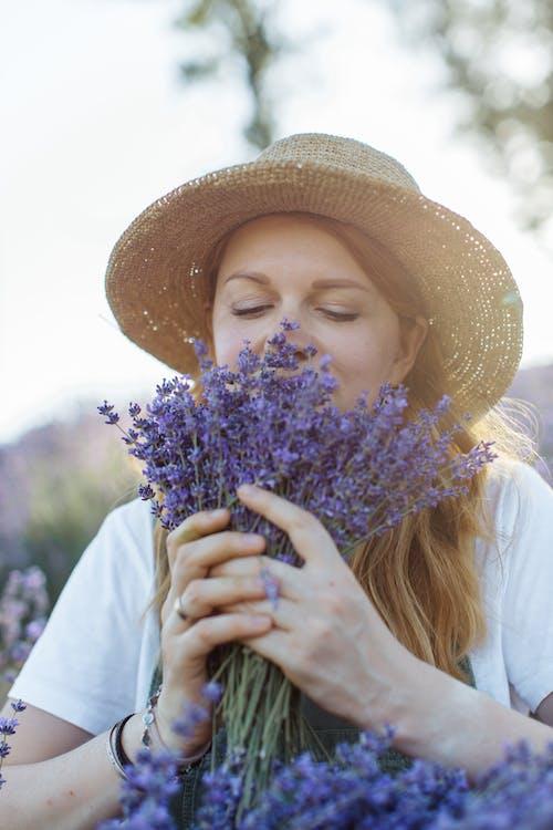 Woman in White Long Sleeve Shirt Holding Purple Flower