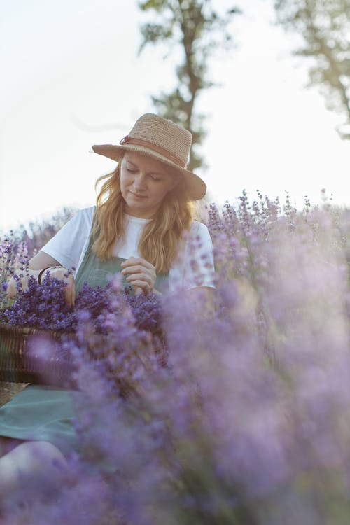 Woman in White and Black Polka Dot Long Sleeve Shirt and White Hat Standing on Purple