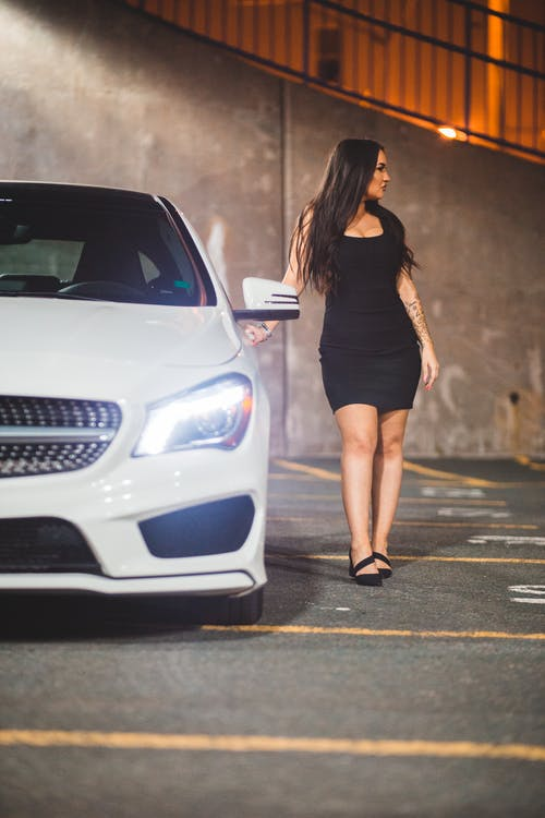 Gorgeous woman by luxury car on parking