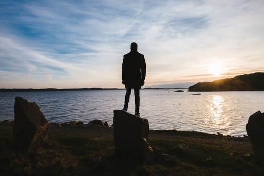 Silhouette of Person Standing on Rock Near Body of Water during Sunset
