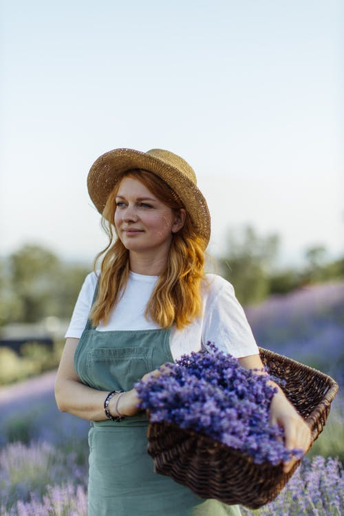 Woman in White Shirt and Brown Hat Holding Purple Flowers