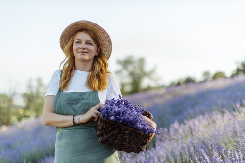 Woman in Blue Dress Wearing Brown Straw Hat Standing on Purple Flower Field