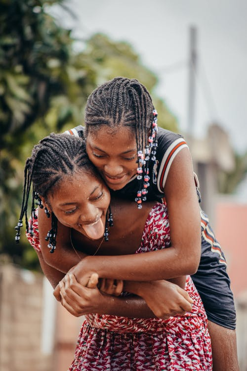 Happy African girlfriends having fun on street