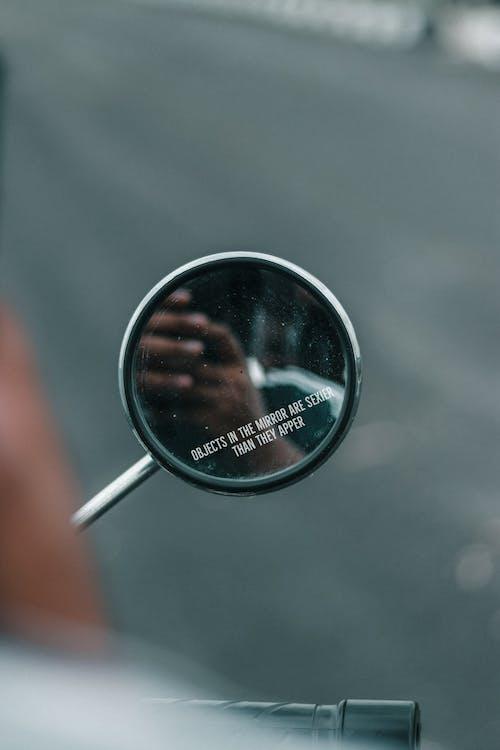 Man driving motorcycle and taking selfie in rearview mirror