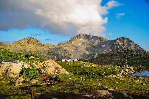 Green Grass Field Near Mountain Under Blue Sky