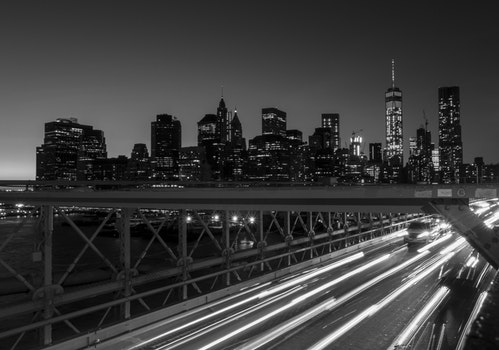 Grey Scale and Time Lapse Photography of a Bridge With Car during Night Time