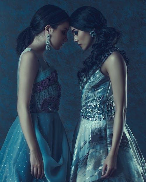 Stylish models in elegant dresses on blue background