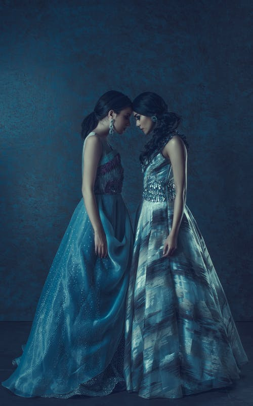 Elegant models in dresses on blue background