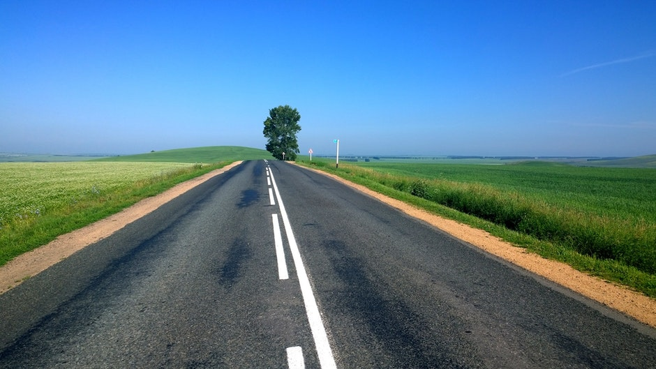 Empty Road Surrounded by Green Grass during Daytime