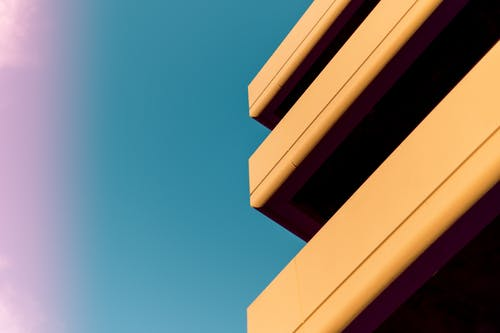 From below of exterior fragment of modern building with big terraces against cloudless blue sky on sunny day