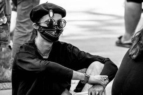 Black and white of unrecognizable male activist in stylish beret sunglasses and face mask sitting on ground on street with placard in hand during strike