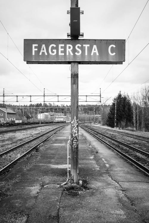 Grayscale Photo of Rail Road Sign