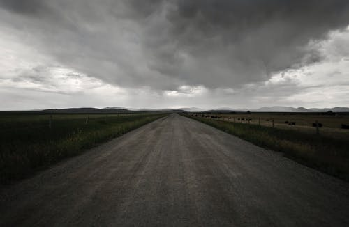 Gray Road Between Green Grass Under Gray Clouds