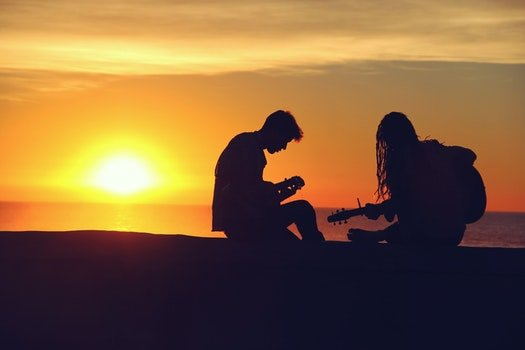 Man and Woman Sitting and Playing Guitar