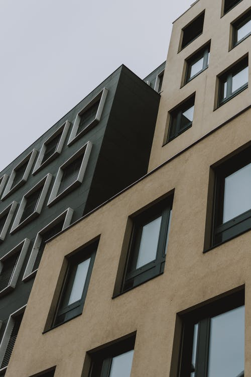 From below contemporary building with brown and black facade and windows against gray sky at daytime