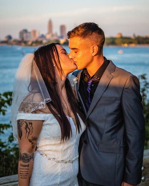 Bride in white dress with veil kissing groom while standing near calm river against blurred background in sunlight in summer