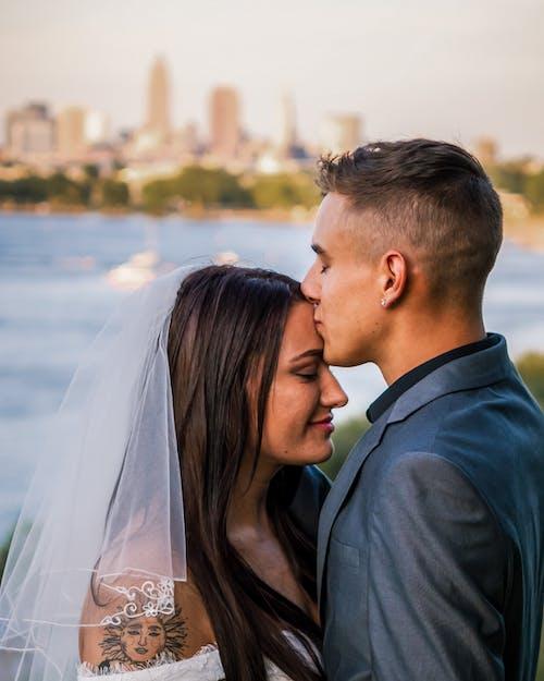 Groom kissing bride in forehead