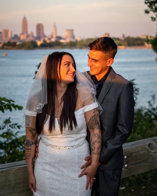 Groom and bride with tattoos standing near water and looking at each other while enjoying wedding celebration in city street