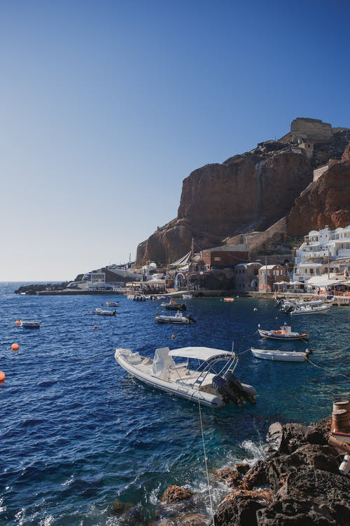 Various boats floating on rippling sea water surrounded by rough rocky cliffs against cloudless blue sky in sunny resort