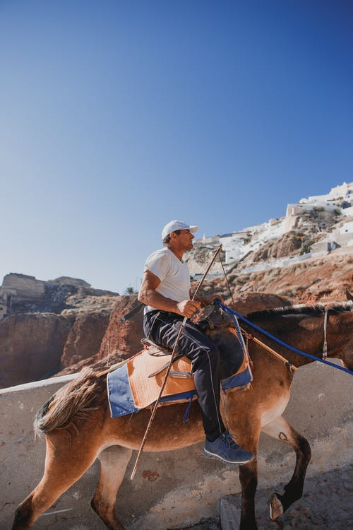 Young man riding horse in rocky terrain on sunny day