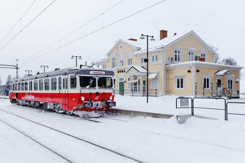 Red and White Cable Cars on Snow Covered Ground