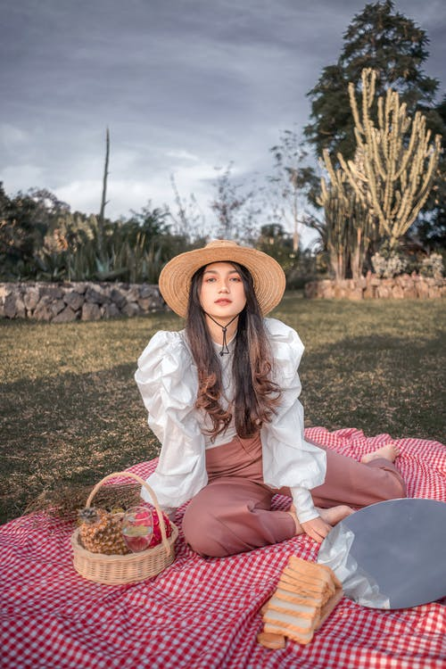 Stylish young female in trendy outfit and straw hat relaxing on plaid on lawn and looking at camera during picnic in green park