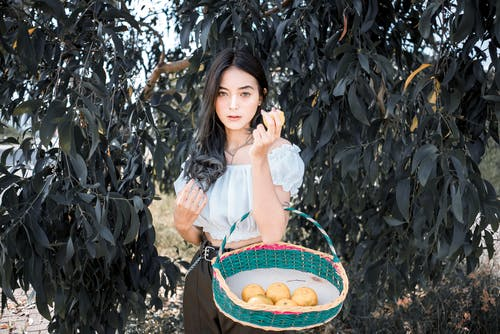 Young ethnic female standing near tree with basket of ripe citruses