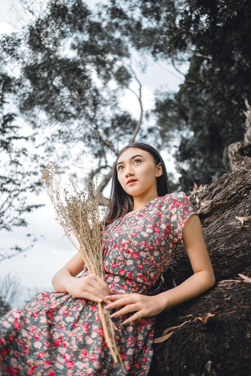 Dreamy young ethnic lady leaning on tree and looking away while relaxing in nature