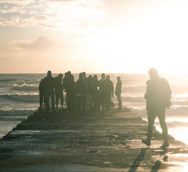 People on Gray Wooden Beach Pathway during Sunset