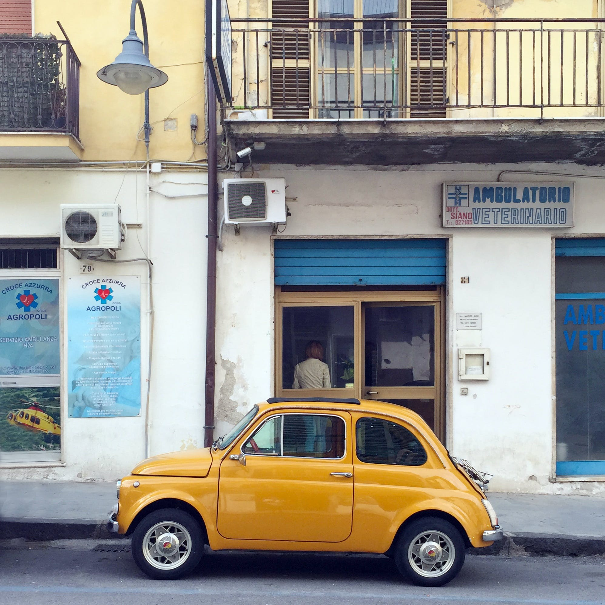 Side of Yellow Classic Fiat 500 Parked in Front of White Building