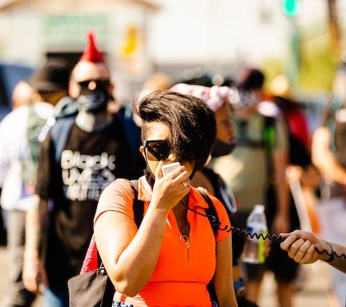 Woman in Orange Tank Top Wearing Black Sunglasses